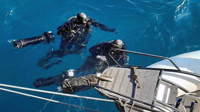 Divers returning to the surface with the watertight bag containing the cocaine