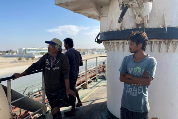 Nay Win, left, and other crew members of MT Iba look out to sea in Umm Al Quwain